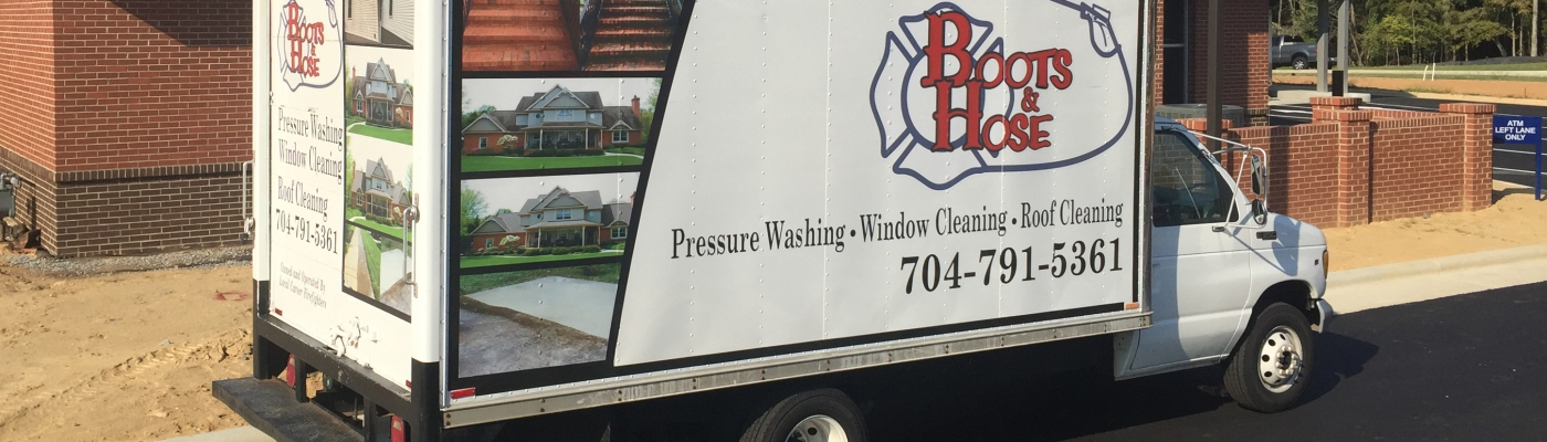 Boots and Hose Pressure Washing truck parked outside of a brick building.
